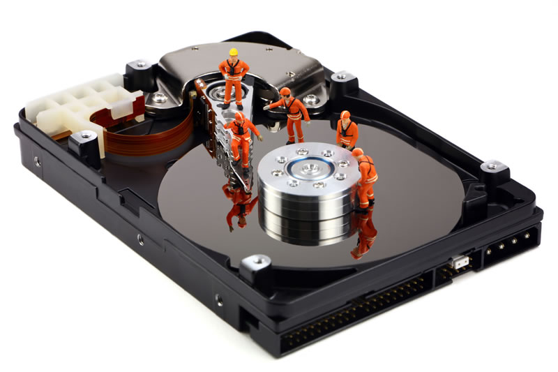Another tech support concept of miniature technicians working on recovering data in a hard drive.